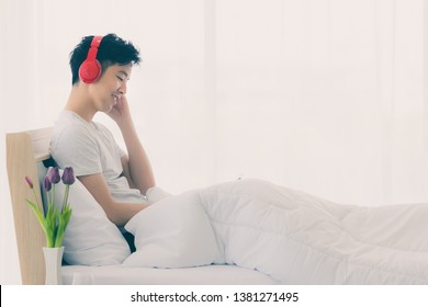 Young Asian man model in pajamas lying in bed and wearing red headphone, listening music from tablet, in bedroom.