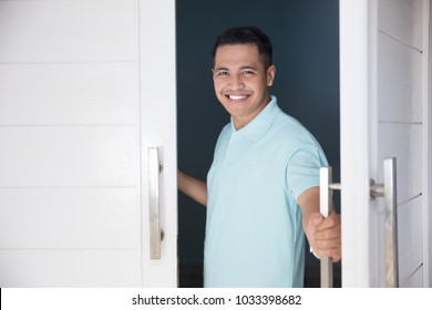 young asian man open his front house door and smiling