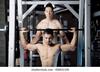 Young asian man and personal trainer with barbell flexing muscles in gym
