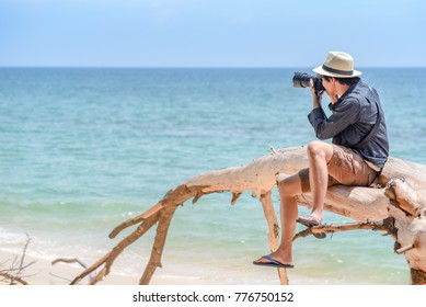 Young Asian man photographer and traveler sitting on white dead tree near sand beach of tropical island taking photos of turquoise sea. Summer holiday and vacation travel. Photography concept