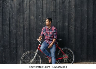 5faaddd7e Young Asian man in a plaid shirt sitting on his bike and leaning against a  dark