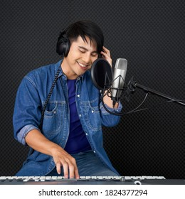 Young asian man playing an electric keyboard in front of black soundproofing walls. Musicians producing music in professional recording studio.
