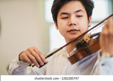 Young Asian man playing violin.