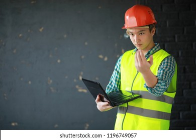 Young Asian man in protective helmet and construction waistcoat