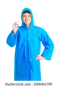 Young Asian man in raincoat showing OK on white background