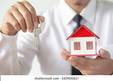 Young Asian man receiving new apartment or room key from realtor or real estate sales agent after finish a rental or buying contract.