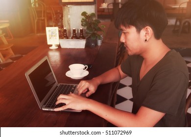 young Asian man relax and working  in coffee shop with soft light and soft focus tone