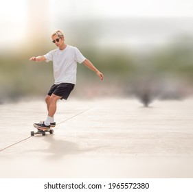 Young asian man riding skateboard on city street blurred background. Male in short pants practice surf skate  board exercise on urban road. Trendy outdoor extreme sport in Thailand though dangerous.