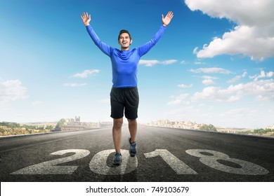 Young asian man running with 2018 number on asphalt road. Happy New Year 2018