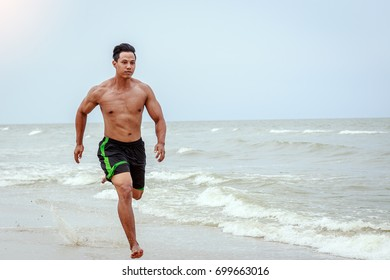 Young Asian man running on the beach with bare feet