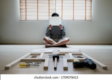 Junge asiatische Menschen selbst montieren Holzmöbel und lesen leeres weißes Papier, um Unterricht zu setzen
