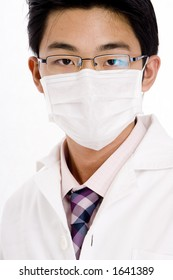 A young asian man in shirt and tie with lab coat and face mask