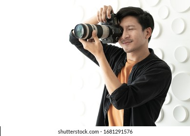 Young Asian man shooting photo by digital camera in photography studio. Portrait of male photographer taking pictures. Camera shooting is happy hobby. Behind the scene of journalist takes photographs.
