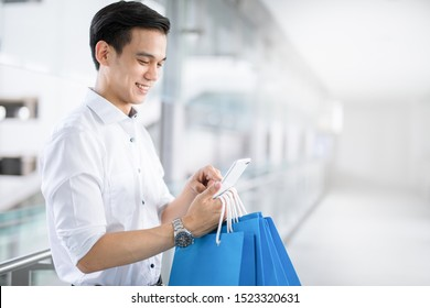 Young Asian man with shopping bags is using a mobile phone and smiling while doing shopping