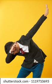 Young asian man showing dab posture isolated on yellow background