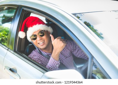Young asian man showing thumbs up while driving car with Christmas Santa hat.