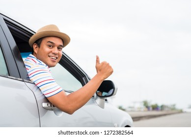 Young asian man showing thumbs up while driving car.