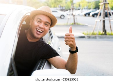 Young asian man showing thumbs up while driving car