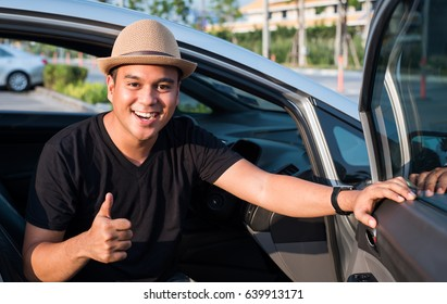 Young asian man showing thumbs up while sitting in the car