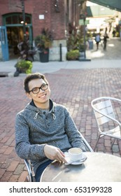 Young asian man sitting and smiling in relaxing outdoor cafe holding cup of coffee, with copy space