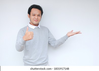Young Asian man is smile and happy with with hand point on empty space