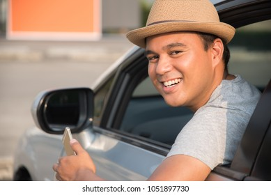 Young asian man smiling while sitting in a car with open front window