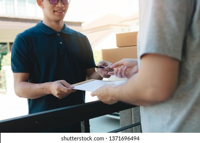 Young asian man smiling while delivering a cardboard box to the woman holding document to signing signature.