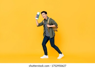 Young Asian man solo traveler with backpack passport and boarding pass ready to fly on isolated yellow background