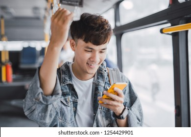 Young asian man is standing in the bus using phone and holding onto the bar while waiting to arrive at her destination.