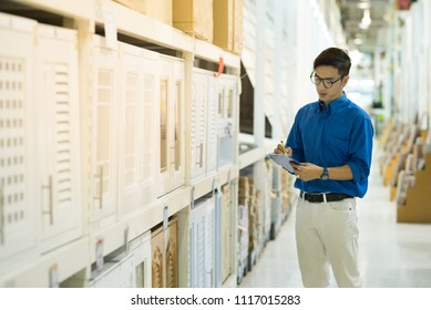 Young Asian man standing checking the shopping list and looking for product in warehouse wholesale, shopping warehousing concept