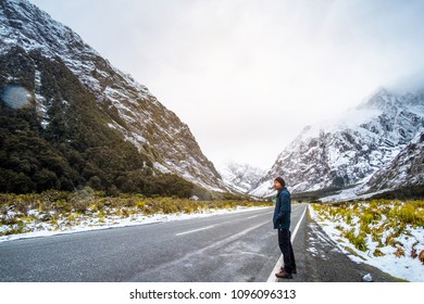 A young Asian man standing on the road among snow mountain.
