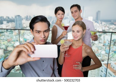 Young Asian Man Taking Selfie Picture with Friends