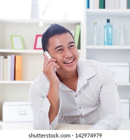 Young Asian man talking on the phone. Lifestyle Southeast Asian man at home. Handsome Asian male model.