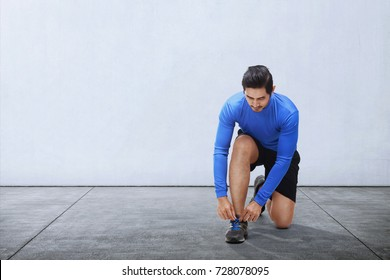 Young asian man tie sport shoe laces before running outdoors