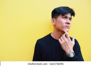 Young Asian man touching his face with facial skin problem about acne moles and pores isolated on yellow background. Feeling worried about his look. Men health and aesthetics concept