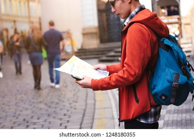 Young  Asian man tourist which travel guide tourism in Europe and looking for way on destination map,enjoying vacation. Tourism, sightseeing, traveling concept
