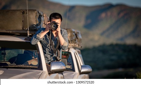 Young Asian man traveler and photographer sitting on the car window taking photo on road trip in Namibia, Africa. Travel photography concept