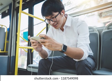 Young Asian man traveler sitting on a bus using smartphone watch video or playing game while smile of happy, transport, tourism and road trip concept.