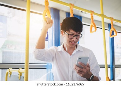 Young Asian man traveler standing on a bus listening to music on smartphone while smile of happy, transport, tourism and road trip concept.
