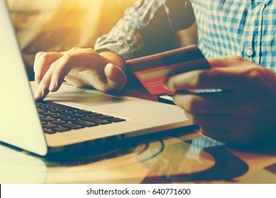 Young asian man typing laptop keyboard and holding credit card at home with online shopping or internet banking concept.