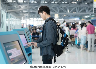 Young Asian man using self check-in kiosks in airport.