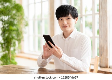 young asian man using smart phone