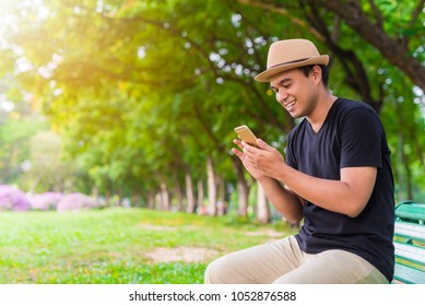 Young asian man using smartphone in park.