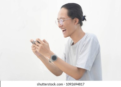 young asian man using smartphone and get excited, young asian man playing game at smartphone