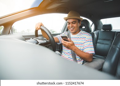 Young asian man using smartphone in car