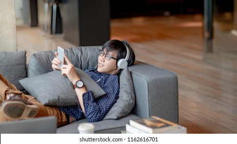 Young Asian man using smartphone for listening to music on mobile application, lying and relaxing on sofa during free time. Urban lifestyle in living space concept