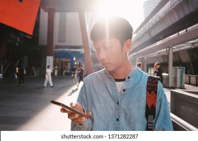 Young asian man using smartphone in the outdoor of shopping mall, urban city lifestyle