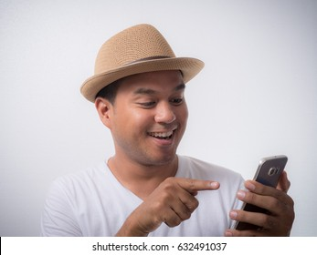 Young asian man using smartphone and Smiling