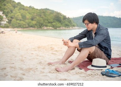 Young Asian man using smartphone on tropical beach, digital nomad lifestyle or freelance occupation concepts