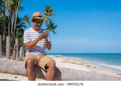 Young asian man using smartphone on the tropical beach
